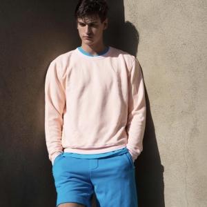 COTTONCITIZENのピンクのスウェットを着た男性
